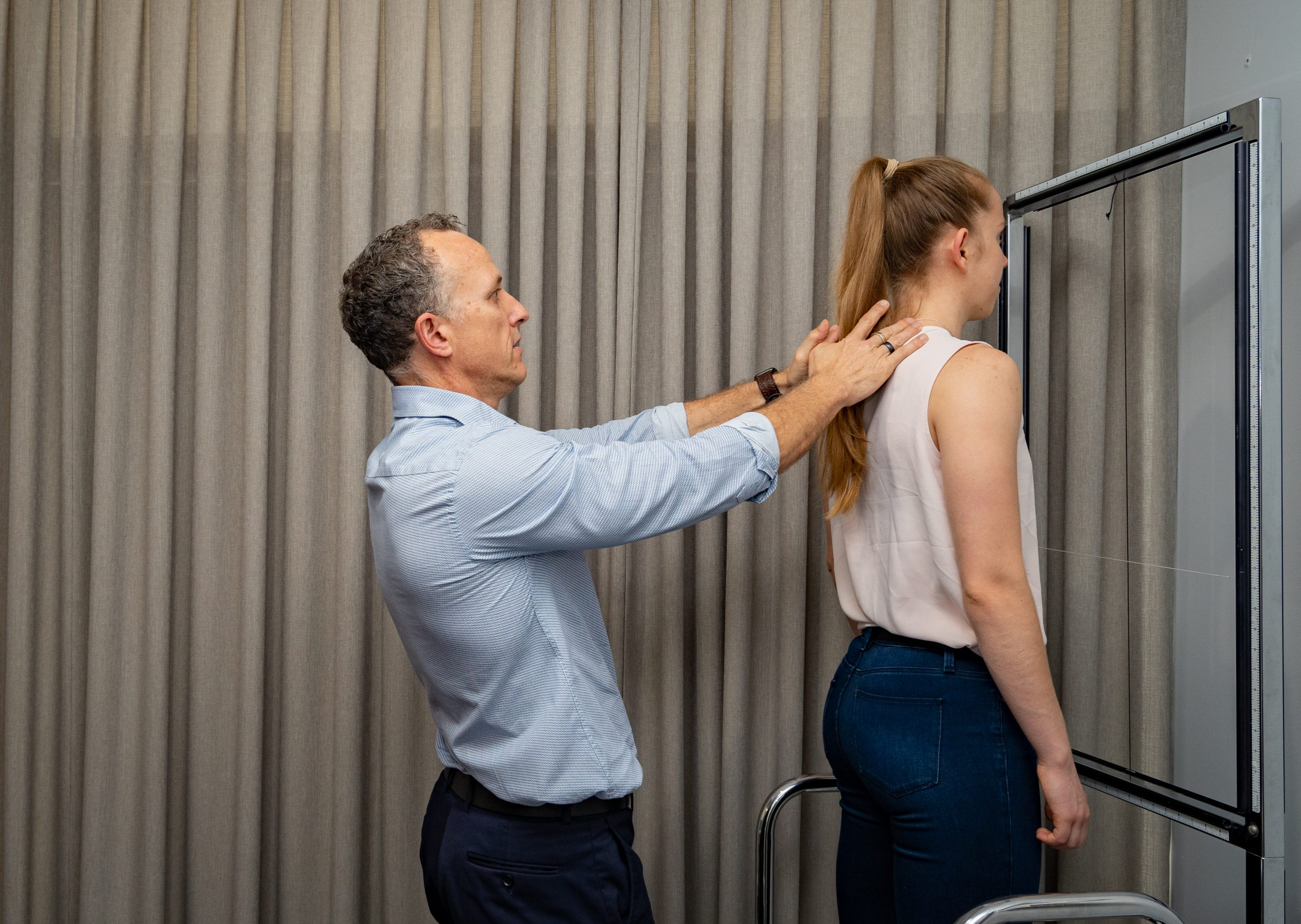 Chiropractor conducting postural analysis on a patient