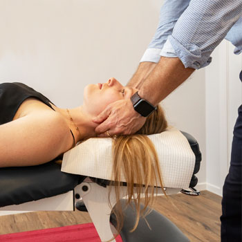 Chiropractor giving neck adjustment to woman